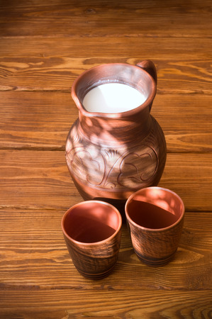 house ware: Clay jug with milk on a wooden table Stock Photo