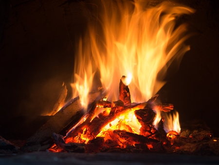 yule log: Fire in fireplace. Closeup of firewood burning in fire Stock Photo