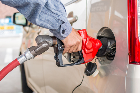 natural gas prices: close up  hand pumping gasoline or fuel into gas tank on car Stock Photo