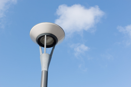 lamp post: lamp post and  fluffy clouds in blue sky background Stock Photo
