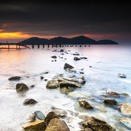 Vista puesta del sol con el embarcadero en la playa