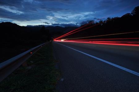 Rastros de la luz de los medios de transporte en las carreteras