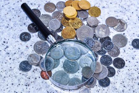 Lupa con un concepto de grupo de monedas. Foto de archivo