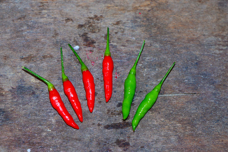 Red and green spice chili on the wooden table. Stock Photo