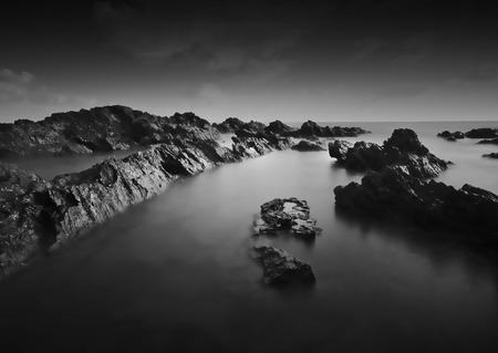 Playa rocosa en blanco y negro. Foto de archivo
