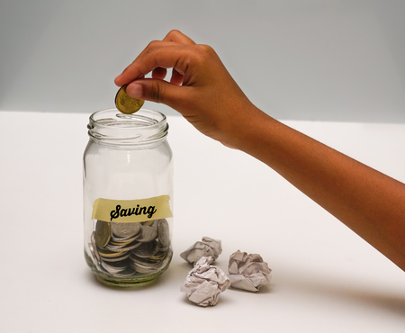 coin bank: Saving Money Concept With Hand Putting Coin On Glass Jar.