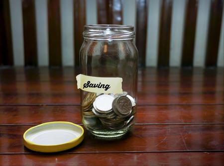 Ahorrar dinero con el concepto del ahorro Etiqueta de texto Escrito el tarro de cristal. Foto de archivo
