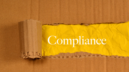 yellow paper: Torn Paper With Word Compliance. Stock Photo