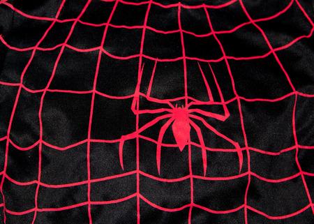 Het patroon van het rode spinwapen beklimt op het doek