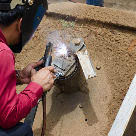 laboring: worker welding metal and sparks
