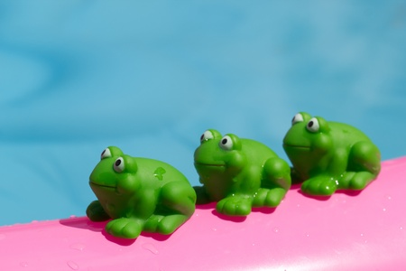 toy green frog on an inflatable pool Stock Photo