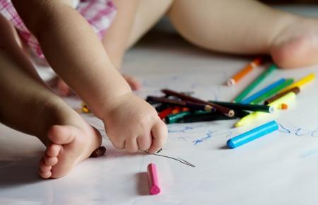 child draws with crayons. closeup