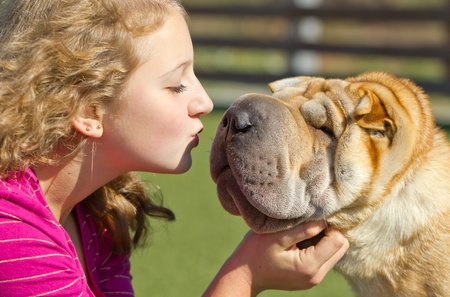 teen girl kissing a dog on a sunny day