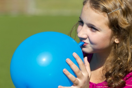 to inflate: teen girl inflates the balloon outdoors