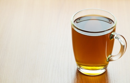 glass cup of tea on a wooden table closeup