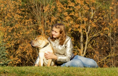 teen girl with dog in autumnal park photo
