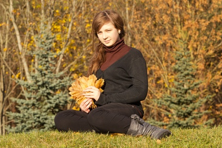 teen girl holding a bunch of leaves in autumn park