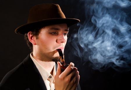A young man smoking a pipe on a black background