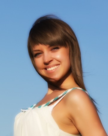 Portrait of girl in white on blue sky background Stock Photo