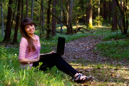 Beautiful girl sitting with a laptop in the forest Stock Photo