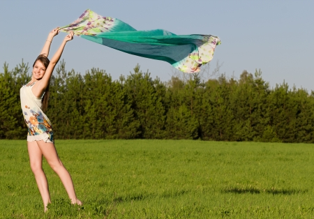 Beautiful young woman on a green meadow with a colored tissue