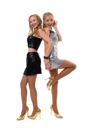 two cute european twin girls dancing in the studio on a white background in shiny dresses - isolated.