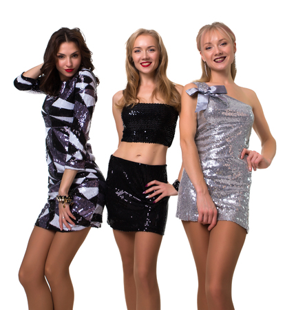 beautiful girls posing in the studio on a white background in shiny dresses - isolated