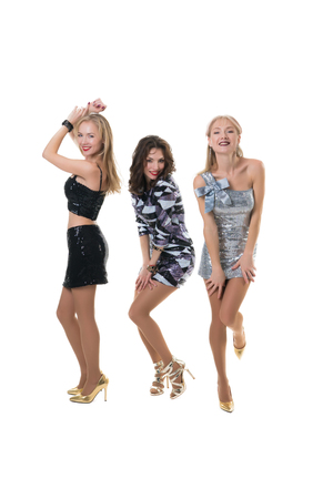 3 beautiful girls at a party dancing on a white background - isolated.