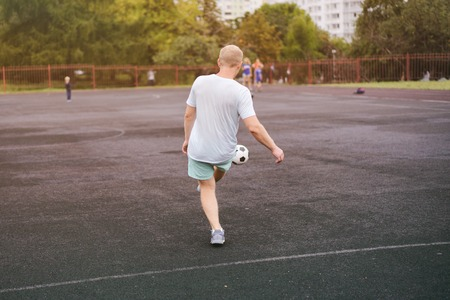 active lifestyle in a modern city - sports man playing with a soccer ball at the stadium Stock Photo