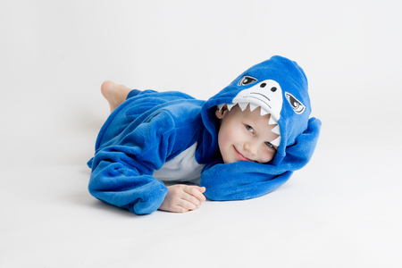 cheerful little boy posing on a white background in pajamas, blue shark costume