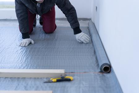 Tischlermeister montiert Kiefernholzboden - umweltfreundlicher Bodenbelag. Kleben der Dämmschicht unter der Verzögerung auf den Beton