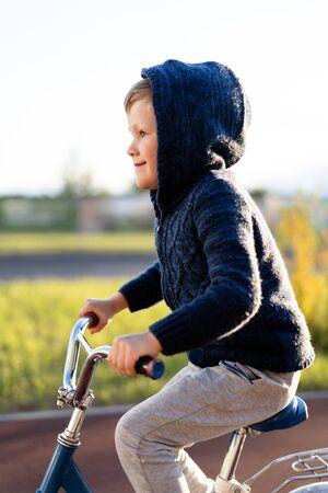 safety in a modern European city. little happy boy rides a bike on a secure rubberized bike path