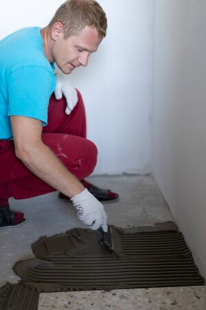 Repair and decoration of apartments and houses. Professionals lay porcelain tiles on the floor in the bathroom.