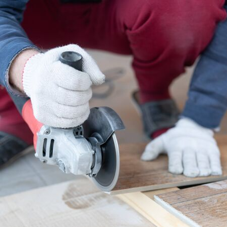 repair and decoration. a man cuts ceramic tiles with a grinder.