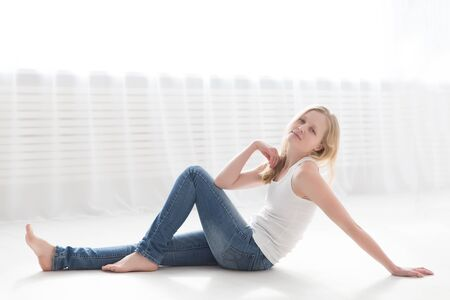 beautiful blonde woman in jeans and a white t-shirt on the floor in a bright room