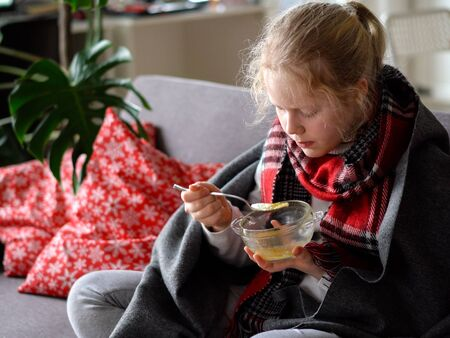portrait of a sick child in a scarf and plaid, girl eating broth on the sofa in the apartment