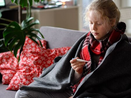 cold caucasian girl at home. portrait of a sick child in a scarf and plaid with a thermometer on the sofa in the apartment