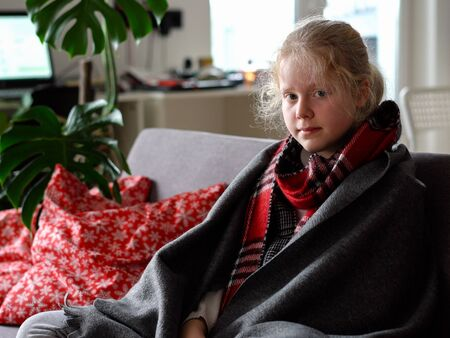 cold caucasian girl at home. portrait of a sick child in a scarf and plaid on the sofa in the apartment