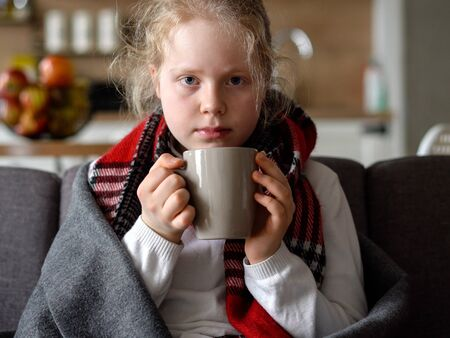 portrait of a sick child in a scarf and plaid with a cup of hot tea on the sofa in the apartment