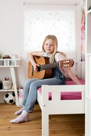 Generation Z - a teenager girl plays the guitar in her room.