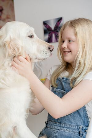 care and love for pets. teenager girl in the home hugs with a golden retriever big dog