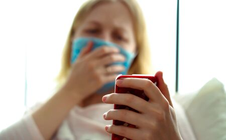 quarantine for coronavirus epidemic. An infected woman in a mask is chatting via video link on a smartphone.