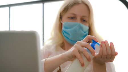 quarantine for coronavirus epidemic. An infected masked woman works at home with a laptop.