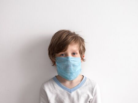 protection against coronavirus. little boy puts a mask on her face.
