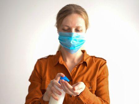 protection against coronavirus. masked woman treats hands with antiseptic