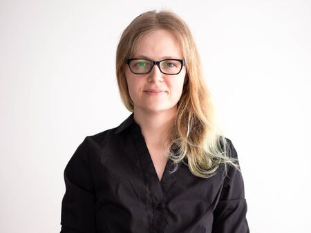 portrait of an office worker in a black shirt and glasses