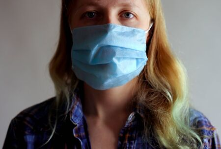 protection against coronavirus. woman puts a mask on her face. Stock Photo