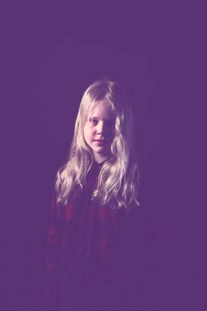 portrait of a blonde teen girl on a black background in studio