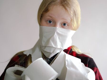 funny photo - quarantined due to an epidemic of coronavirus. masked girl with rolls of toilet paper posing on gray background. Stock Photo