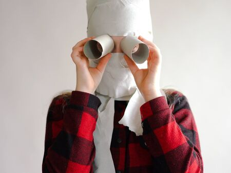 funny photo - quarantined due to an epidemic of coronavirus. girl in a mask from toilet paper posing on a gray background.